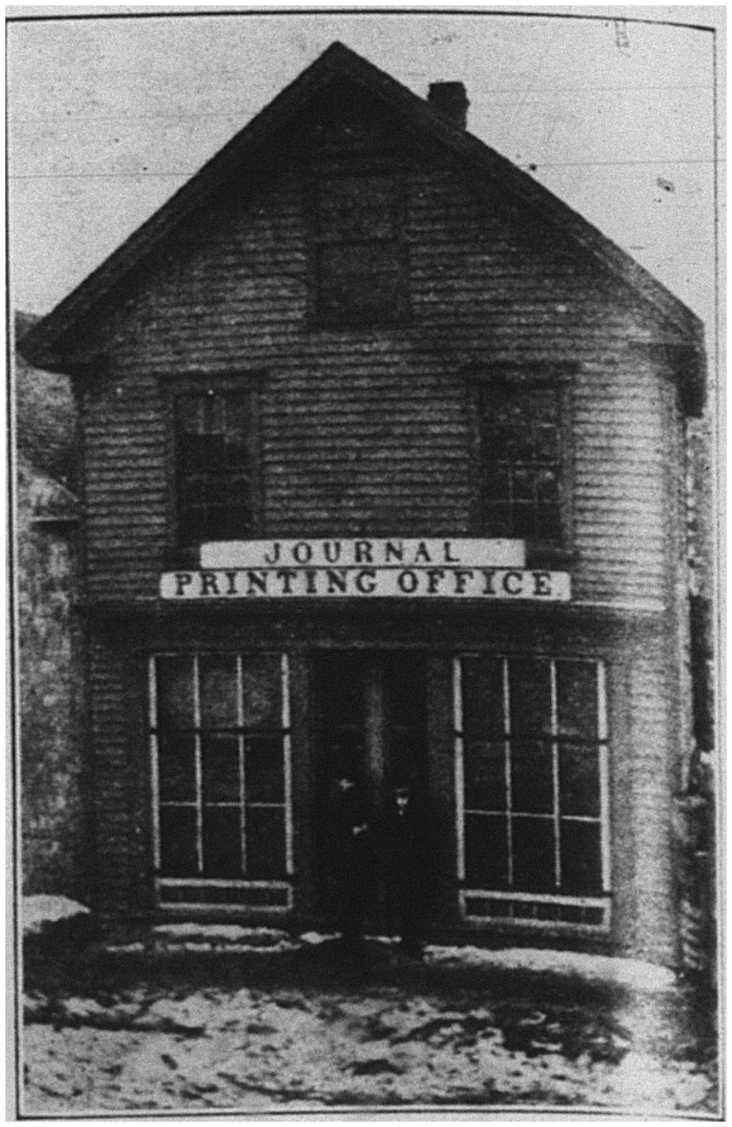 Photograph of the Summerside Journal's Printing Office (built c.1865) taken around 1877. The two individuals standing in the doorway are unidentified.